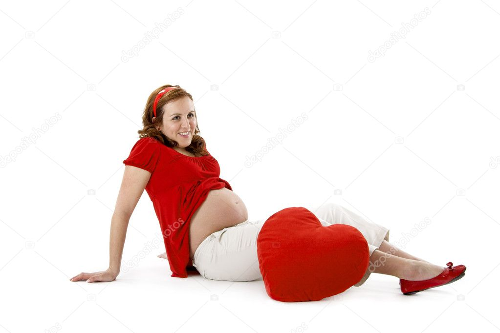 Beautiful pregnant woman enjoying this wonderful moment with a red Heart — Stock Photo #4936787