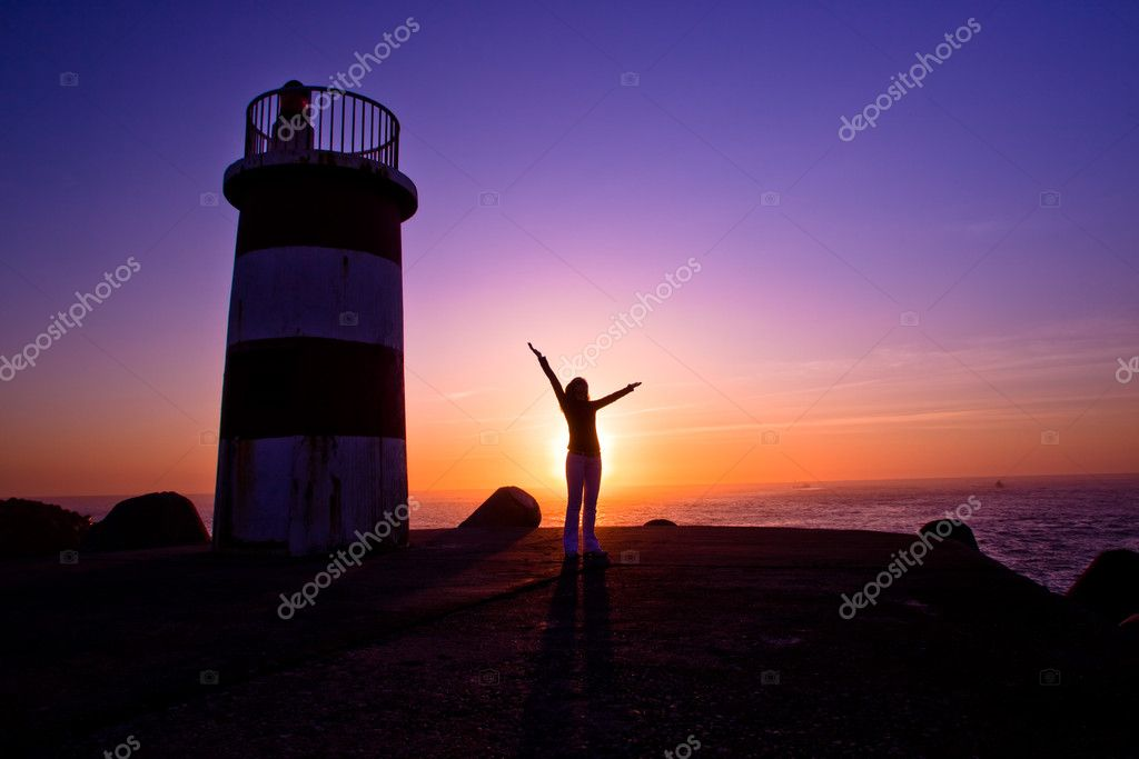Beautiful landscape picture of a lighthouse and a woman looking the sunset — Stock Photo #4940843