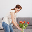 Woman at home holding flowers — Stock Photo #5066585