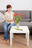 Woman at home holding flowers — Stock Photo