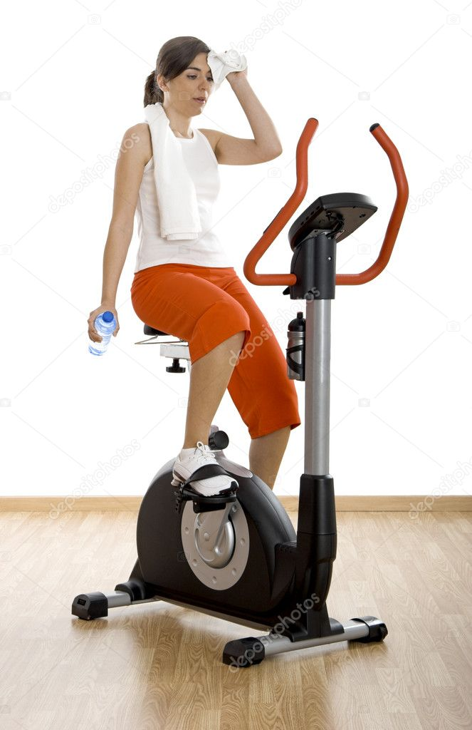 Young woman tired of training on exercise bike at the gym   Stock Photo #5064529