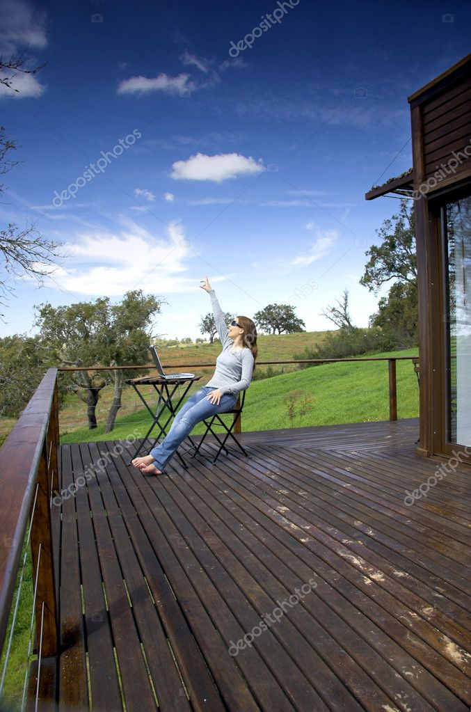 Woman enjoying a beautiful day with a laptop on her home-field — Stock Photo #5064941