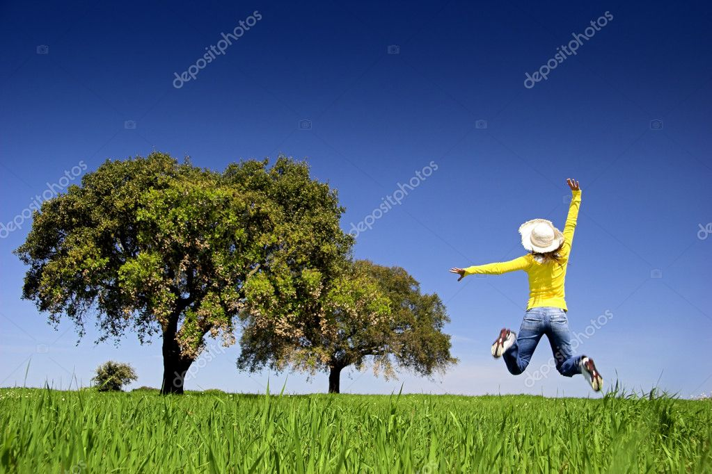 Haapy woman jumping on a beautiful green meadow with trees — Stock Photo #5065298