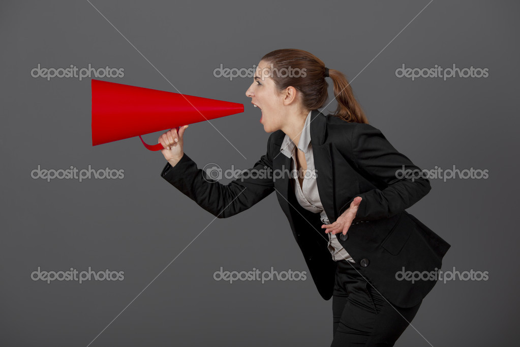 Business young woman speaking to a megaphone, over a grey background — Stock Photo #5067705