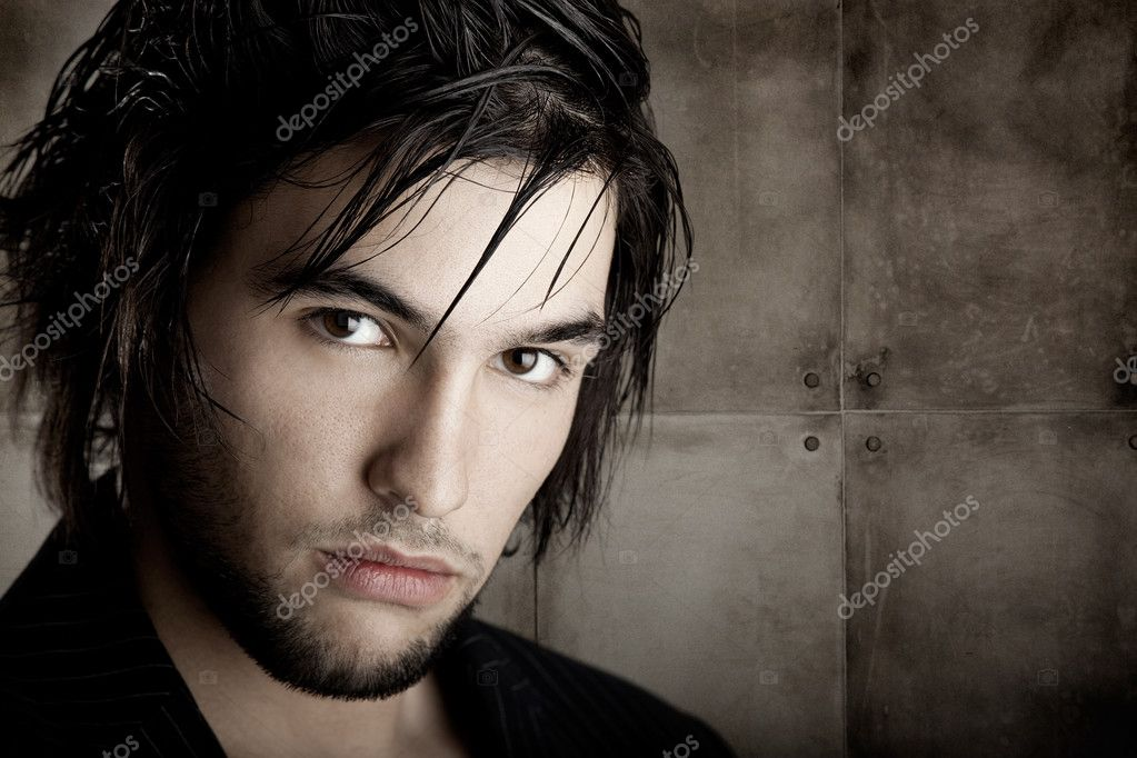 Good looking  young man with modern HairStyle over a grunge wall background  Stock Photo #5074475