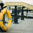 Yellow life buoy on fence — Stock Photo