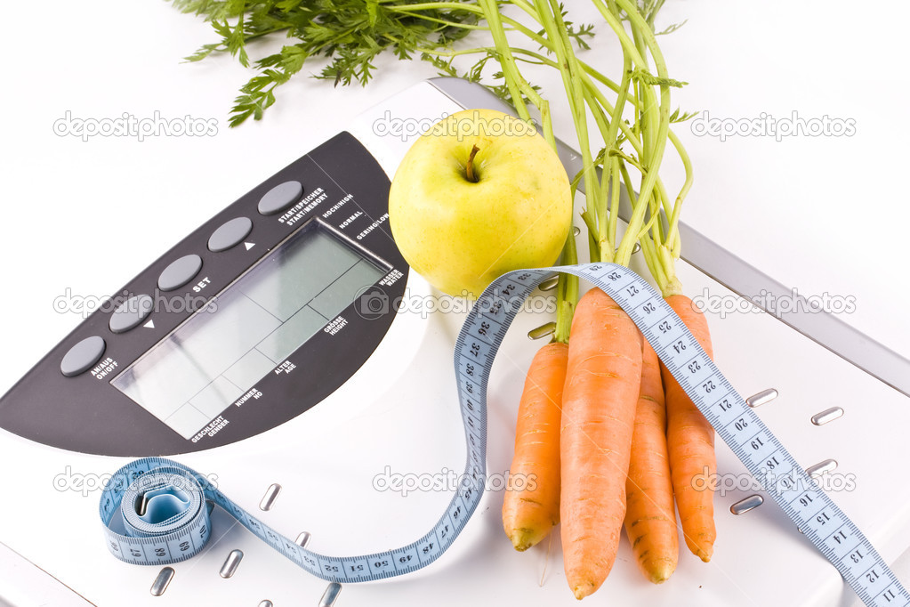 Carrots and apple surrounded by a measuring tape on a white bathroom scale. Blank display.   Stock Photo #3898824