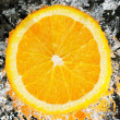 Fresh orange in streaming water - Stock Photo