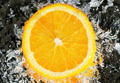 Fresh orange in streaming water — Stock Photo