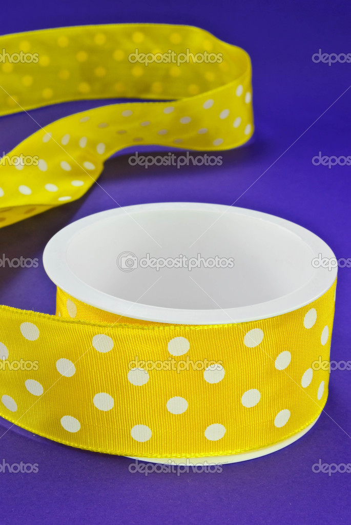 Yellow with white polka dots spool of ribbon on a purple background — Stock Photo #3330540