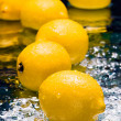 Lemons on thin layer of water — Stock Photo