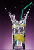 Sliced lemon falling in glass of drink — Stock Photo