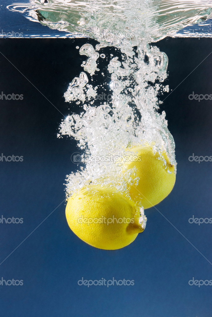 White bubbles from a couple of lemons sunk in water against a dark blue background  Stock Photo #2854639
