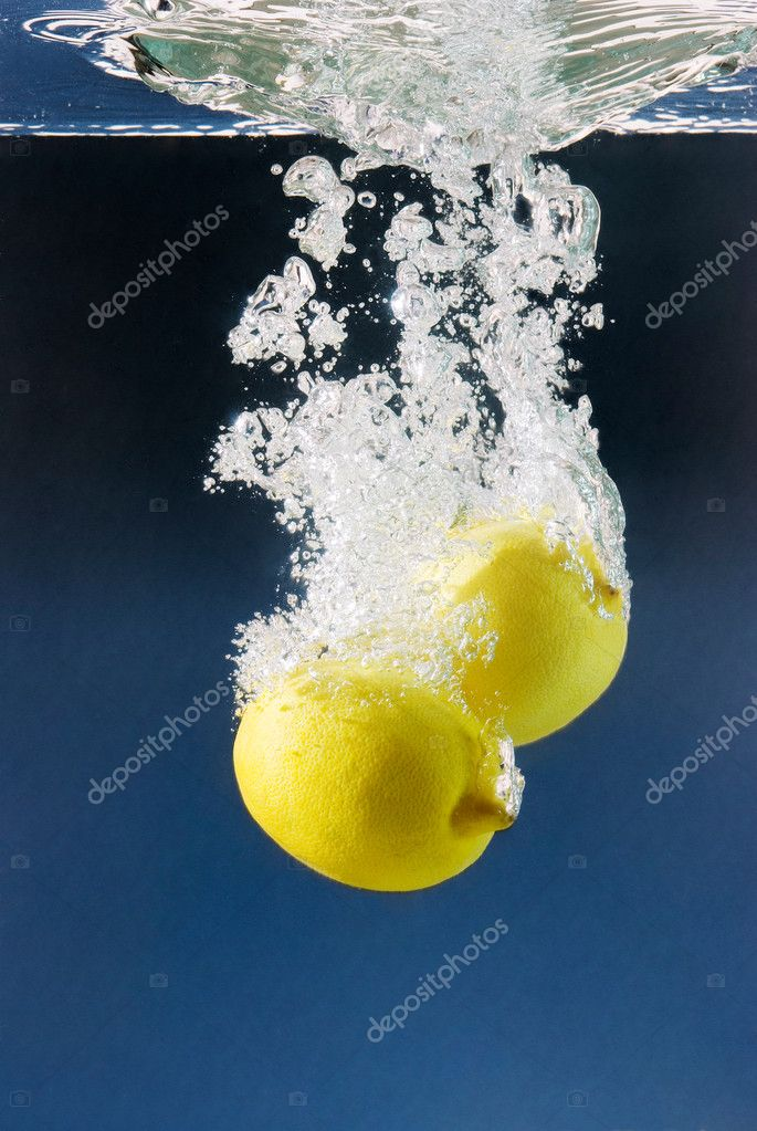 White bubbles from a couple of lemons sunk in water against a dark blue background  Photo #2854639
