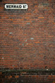 Mermaid street brick wall background — Stock Photo
