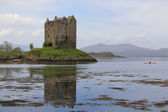 Kayak explores castle stalker scotland — Stock Photo