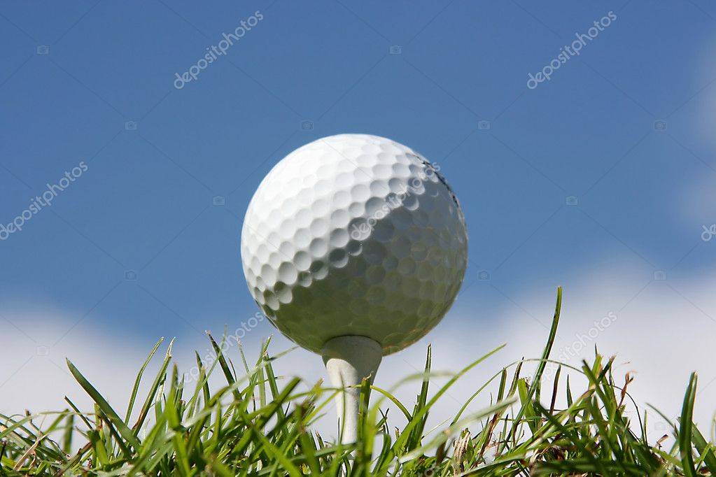 Golf ball on grass against a blue sky and white clouds — Stock Photo #2843697