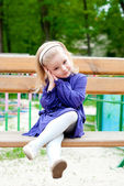 Small girl on a bench — Stock Photo