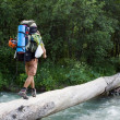 Backpacker crossing the river. — Stock Photo