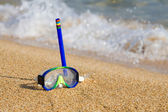 Tube and mask for a scuba diving on seacoast with a pebble — Stock Photo