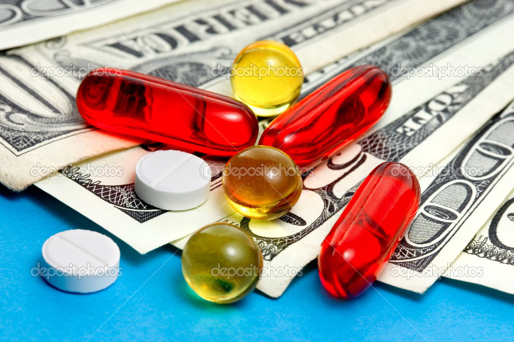 Tablets and pills on dollar banknotes — Stock Photo #3546270