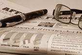 Glassess and pen on financial newspaper — Stock Photo