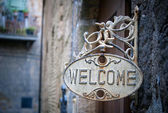 Welcome sign on log home — Stock Photo