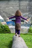 Little girl balancing on a bole — Stock Photo