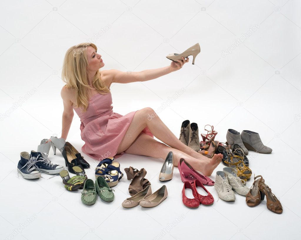 Happy young blond woman sitting on the floor surrounded by shoes — Stok fotoğraf #3324313