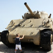 Child tries to stop tank — Stock Photo