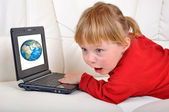 Girl is amazed by Earth in notebook — Stock Photo