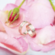 Foto Stock: Rose and wedding rings with drops of watter
