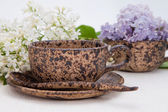 Ceramic cup and lilac — Stock Photo