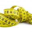 Stock Photo: Curled yellow measuring tape on white