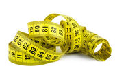 Curled yellow measuring tape on white — Stock Photo