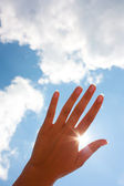 Woman's hand against the sky — Stock Photo