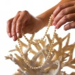 Stock Photo: Pearl necklace in her hands against backdrop of coral