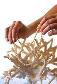 Eine Perlenkette in ihren Händen vor dem Hintergrund der Koralle — Stockfoto