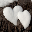 Two snow hearts on rock - Zdjęcie stockowe