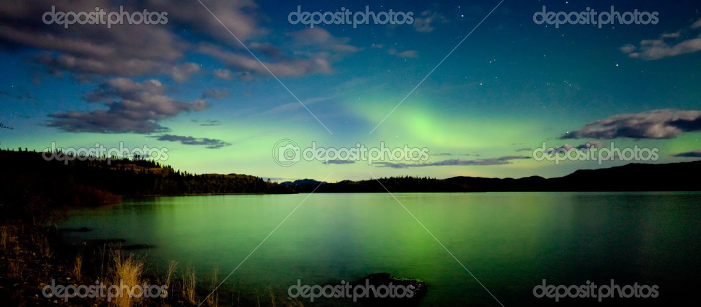 Intense Aurora borealis in moon lit night being mirrored on Lake Laberge, Yukon T., Canada. — Foto Stock #3891704