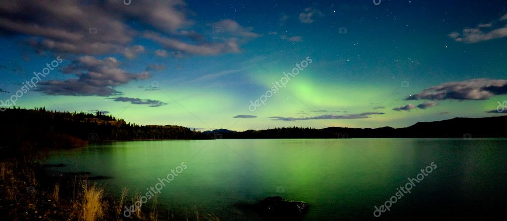 Intense Aurora borealis in moon lit night being mirrored on Lake Laberge, Yukon T., Canada. — Stockfoto #3891704
