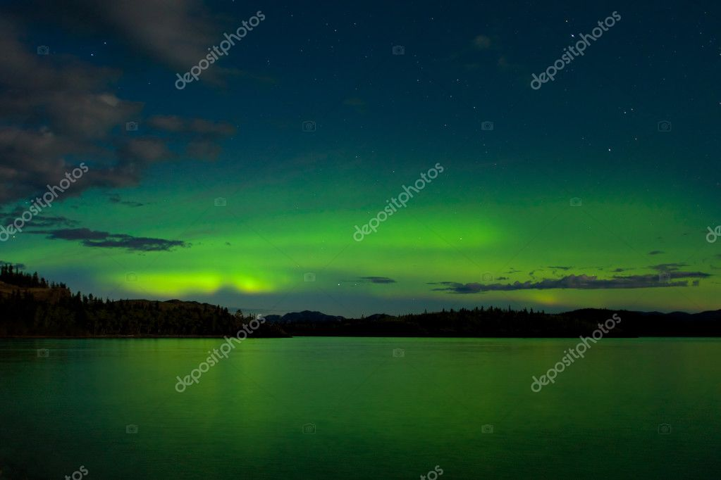Intense Aurora borealis in moon lit night being mirrored on Lake Laberge, Yukon Territory, Canada. — Stock Photo #3891712