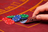 Hand with cards and chips on the table — Stock Photo