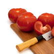 Sliced and whole tomatoes and knife on breadboard — Stock Photo