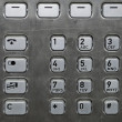 Stock Photo: Metallic number pad on a public phone