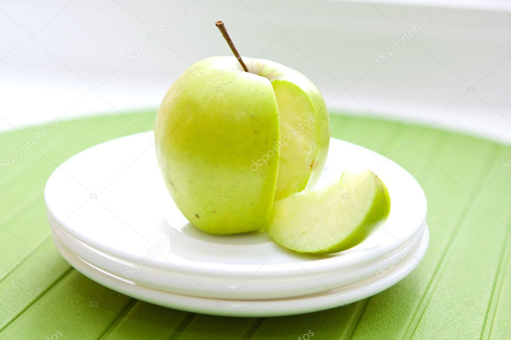 Close up green apple and a slice on the white plates — Stock Photo #2824878