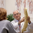 Chiropractor in his office with patient — Stock Photo