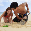 Couple on the beach in hawaii digging — Stock Photo