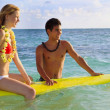 Stock Photo: Beach boy teaches surfing to girl