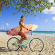 Girl on her bicycle with surfboard — Stock Photo